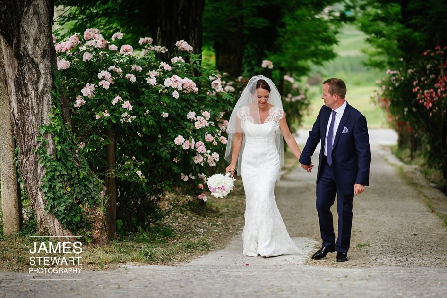 bride and groom walking up a tree lined drive