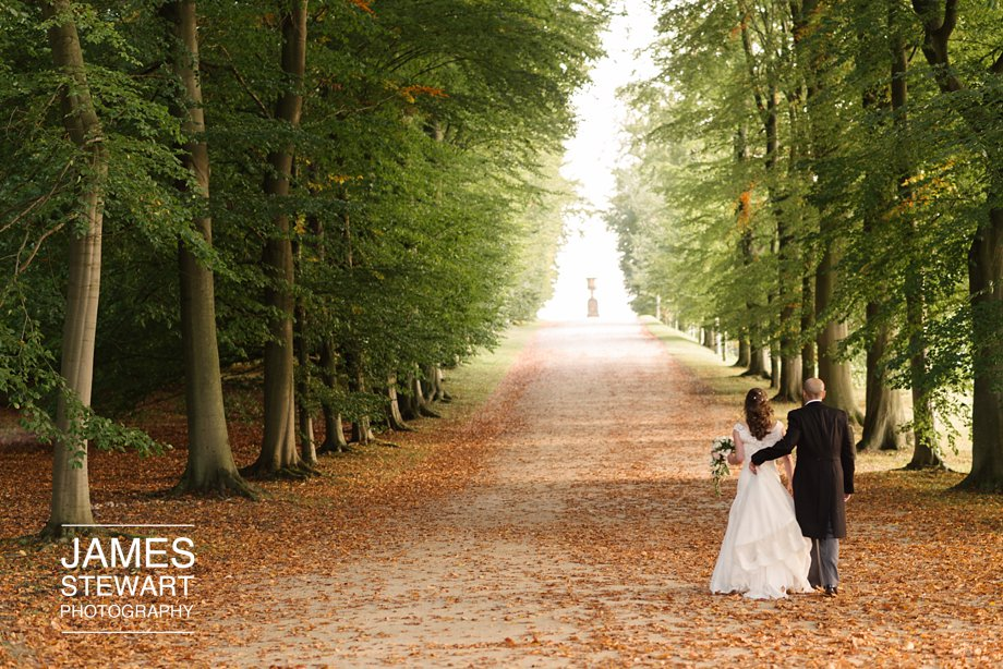 bride and groom walk up the avenue at chatsworth