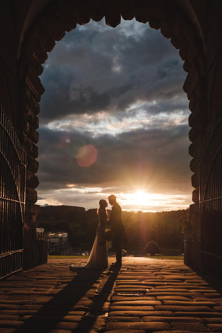 a bride and groom stood in the archway to chatsworth stables with a sunset in the background
